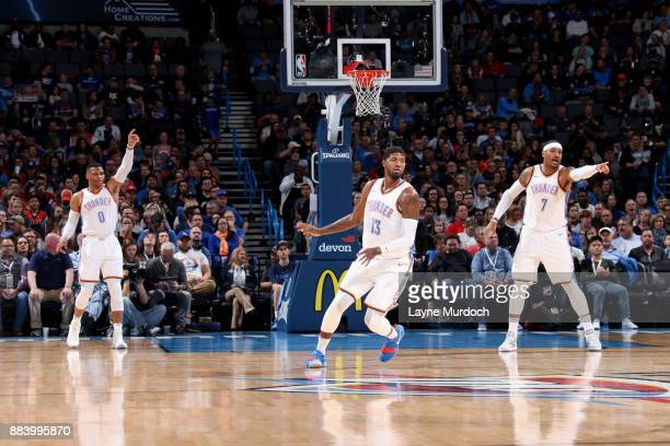 Russell Westbrook Carmelo Anthony and Paul George of the Oklahoma City Thunder play defense against the Minnesota Timberwolves on December 1 2017 at...