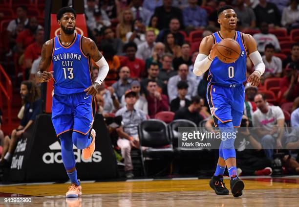 Russell Westbrook moves the ball up the court with Paul George of the Oklahoma City Thunder during the game against the Miami Heat at American...