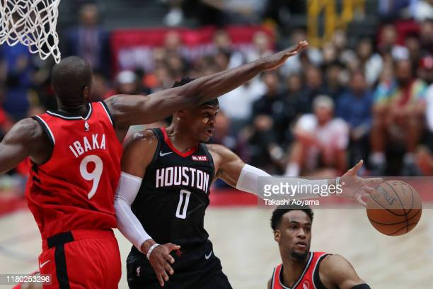 Russell Westbrook of Houston Rockets passes the ball against Serge Ibaka of Toronto Raptors during the preseason game between Toronto Raptors and...