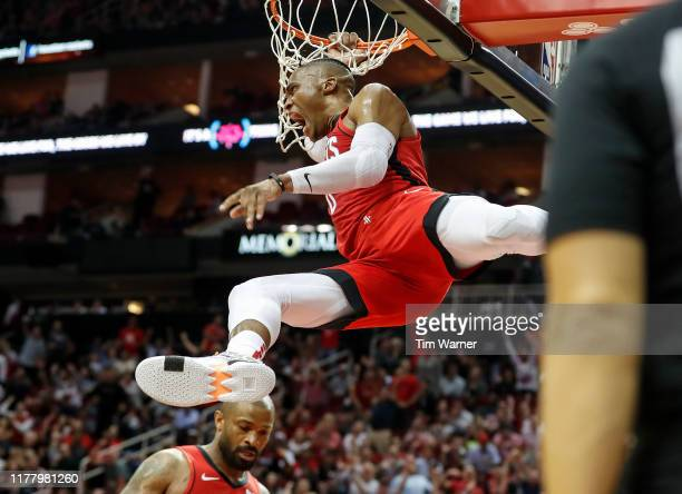 Russell Westbrook of the Houston Rockets dunks the ball defended by Ersan Ilyasova of the Milwaukee Bucks in the second half at Toyota Center on...