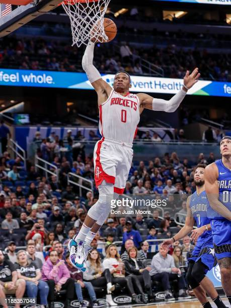 Russell Westbrook of the Houston Rockets goes up for a dunk Michael CarterWilliams and Aaron Gordon of the Orlando Magic during the game at the Amway...