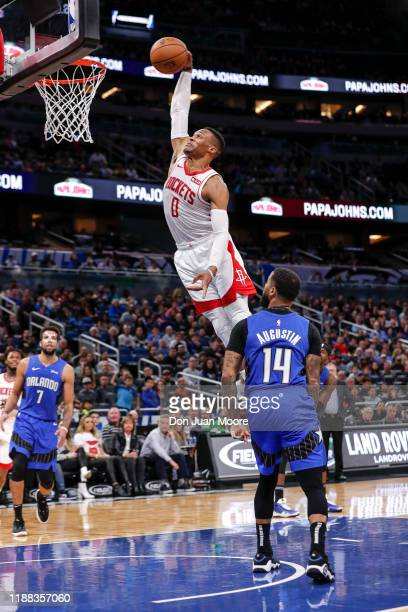 Russell Westbrook of the Houston Rockets goes up for a dunk over DJ Augustin of the Orlando Magic during the game at the Amway Center on December 13...