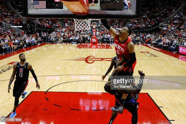 Russell Westbrook of the Houston Rockets goes up for a dunk while defended by Montrezl Harrell of the LA Clippers in the second half at Toyota Center...