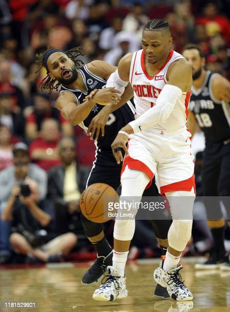 Russell Westbrook of the Houston Rockets is pressured by Patty Mills of the San Antonio Spurs during the first quarter at Toyota Center on October 16...