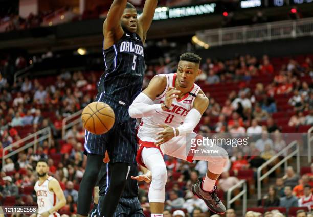 Russell Westbrook of the Houston Rockets passes the ball under the basket while defended by Mo Bamba of the Orlando Magic in the second half at...
