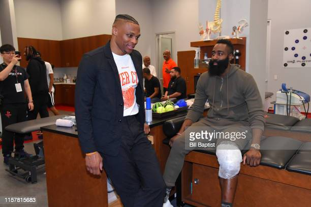 Russell Westbrook of the Houston Rockets talks with James Harden of the Houston Rockets before the Houston Rockets Introductory Press Conference on...