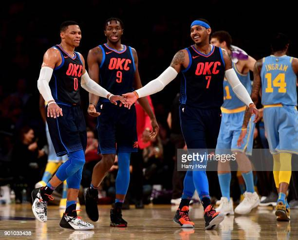Russell Westbrook of the Oklahoma City Thunder celebrates a lead over the Los Angeles Lakers with Carmelo Anthony and Jerami Grant at the end of the...