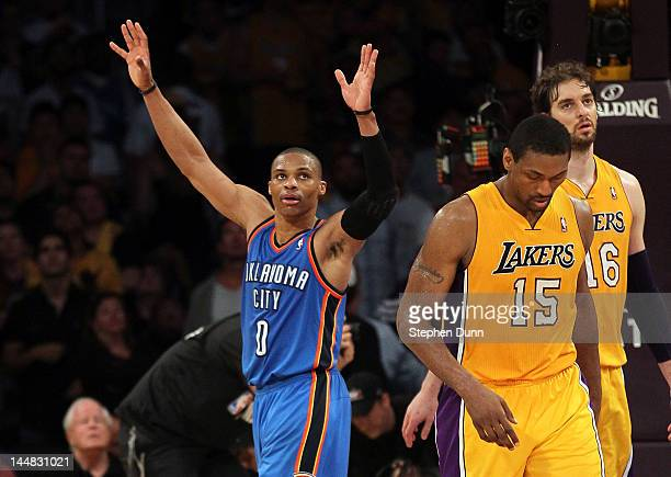 Russell Westbrook of the Oklahoma City Thunder celebrates as Metta World Peace of the Los Angeles Lakers walks with his head down after the Thunder...