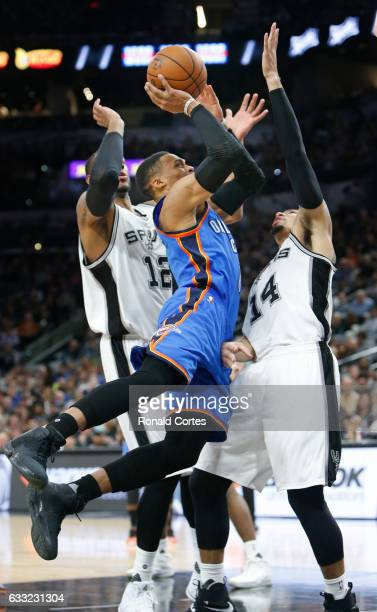 Russell Westbrook of the Oklahoma City Thunder charges over Danny Green of the San Antonio Spurs while LaMarcus Aldridge of the San Antonio Spurs...