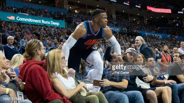 Russell Westbrook of the Oklahoma City Thunder climbs over fans during the first half of a NBA game agains the Sacramento Kings at the Chesapeake...
