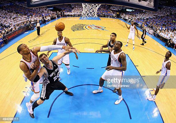 Russell Westbrook of the Oklahoma City Thunder defends Tiago Splitter of the San Antonio Spurs in the second half during Game Four of the Western...