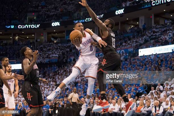 Russell Westbrook of the Oklahoma City Thunder drives around James Harden of the Houston Rockets for two points during the second half of Game Three...