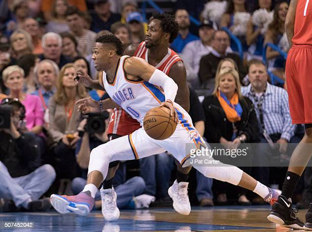 Russell Westbrook of the Oklahoma City Thunder drives around Patrick Beverley of the Houston Rockets looking for a shot during the first quarter of a...