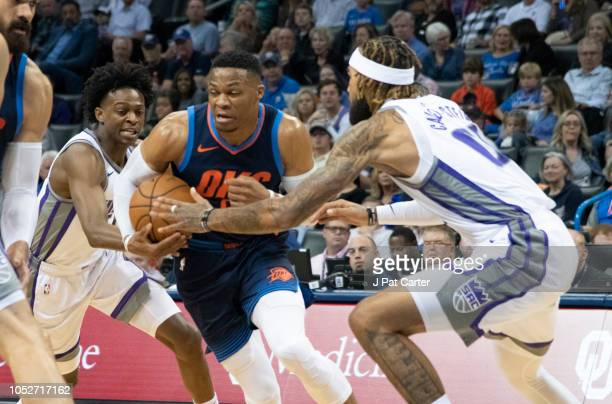 Russell Westbrook of the Oklahoma City Thunder drives around Willie CauleyStein and De'Aaron Fox of the Sacramento Kings during the first half of a...