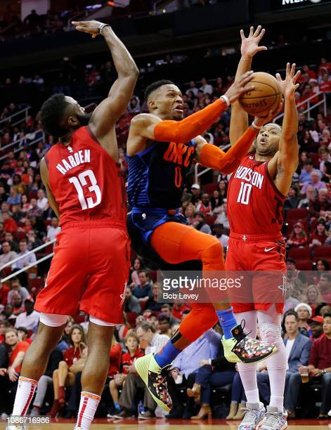 Russell Westbrook of the Oklahoma City Thunder drives between James Harden of the Houston Rockets and Eric Gordon during the fourth quarter at Toyota...