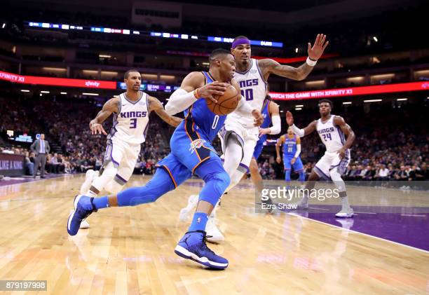 Russell Westbrook of the Oklahoma City Thunder drives on George Hill and Willie CauleyStein of the Sacramento Kings at Golden 1 Center on November 7...