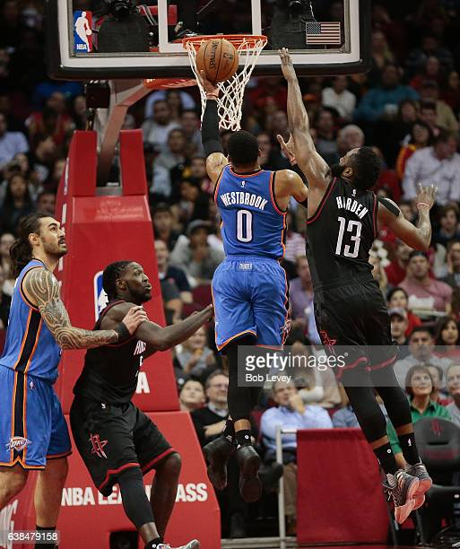Russell Westbrook of the Oklahoma City Thunder drives past James Harden of the Houston Rockets for a layup as Montrezl Harrell and Steven Adams look...