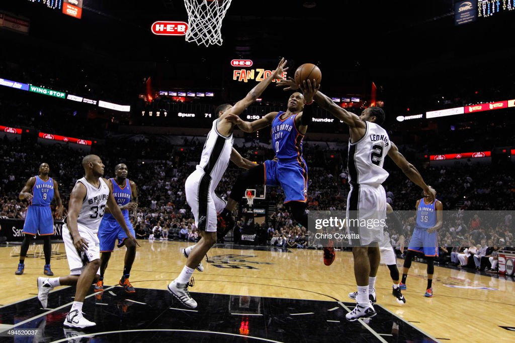 Russell Westbrook #0 of the Oklahoma City Thunder drives to the basket against Tim Duncan #21 and Kawhi Leonard #2 of the San Antonio Spurs in the second half during Game Five of the Western Conference Finals of the 2014 NBA Playoffs at AT&T Center on May 29, 2014 in San Antonio, Texas.