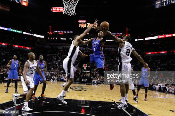 Russell Westbrook of the Oklahoma City Thunder drives to the basket against Tim Duncan and Kawhi Leonard of the San Antonio Spurs in the second half...