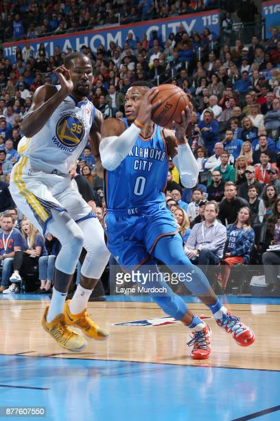 Russell Westbrook of the Oklahoma City Thunder drives to the basket against Kevin Durant of the Golden State Warriors on November 22 2017 at...