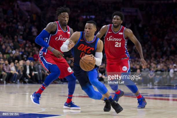 Russell Westbrook of the Oklahoma City Thunder drives to the basket against Robert Covington and Joel Embiid of the Philadelphia 76ers in the first...