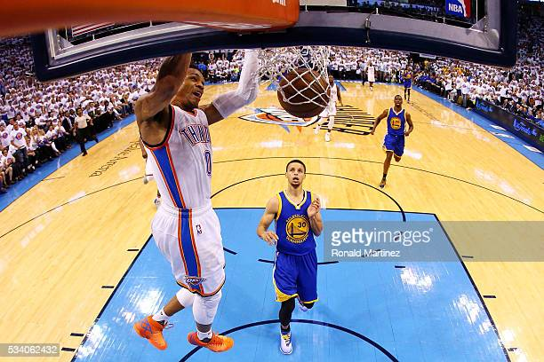 Russell Westbrook of the Oklahoma City Thunder dunks against Stephen Curry of the Golden State Warriors in the first half in game four of the Western...