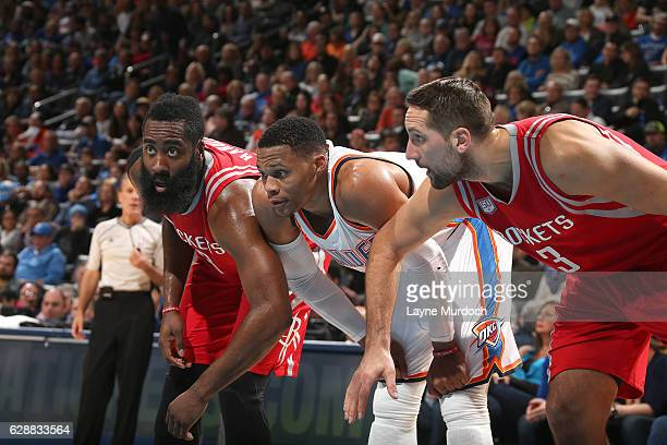 Russell Westbrook of the Oklahoma City Thunder fights for position against James Harden and Ryan Anderson of the Houston Rockets on December 9 2016...