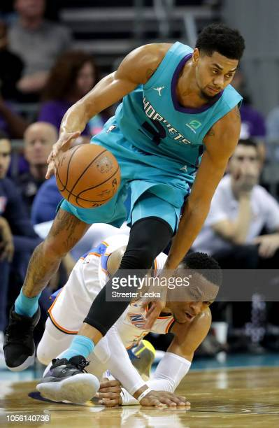 Russell Westbrook of the Oklahoma City Thunder goes after the ball against Jeremy Lamb of the Charlotte Hornets during their game at Spectrum Center...