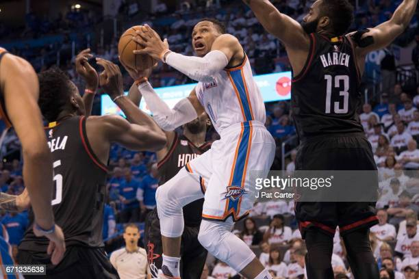 Russell Westbrook of the Oklahoma City Thunder goes between Clint Capela of the Houston Rockets and James Harden of the Houston Rockets for two...