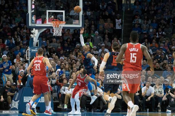 Russell Westbrook of the Oklahoma City Thunder goes over Eric Gordon of the Houston Rockets for two points during the second half of a NBA game at...