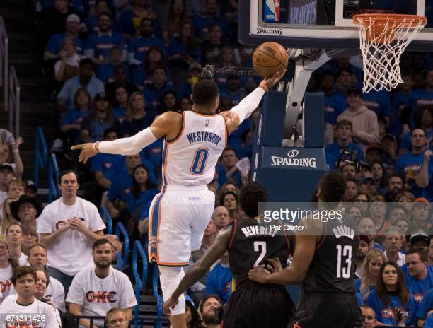 Russell Westbrook of the Oklahoma City Thunder goes over Patrick Beverley of the Houston Rockets and James Harden of the Houston Rockets for two...