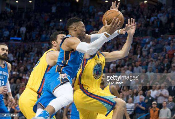 Russell Westbrook of the Oklahoma City Thunder goes over Zaza Pachulia of the Golden State Warriors and Klay Thompson of the Golden State Warriors...