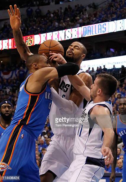 Russell Westbrook of the Oklahoma City Thunder goes up for a shot against both Tyson Chandler and Jose Juan Barea of the Dallas Mavericks in the...