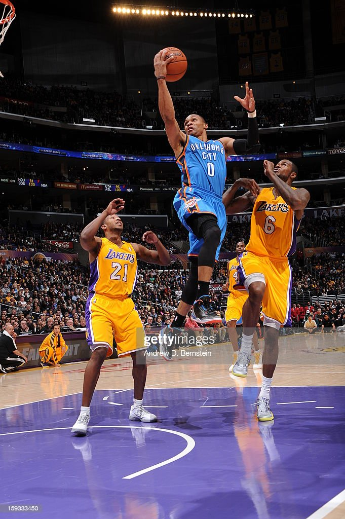 Russell Westbrook #0 of the Oklahoma City Thunder goes up for a shot against Chris Duhon #21 and Earl Clark #6 of the Los Angeles Lakers at Staples Center on January 11, 2013 in Los Angeles, California.