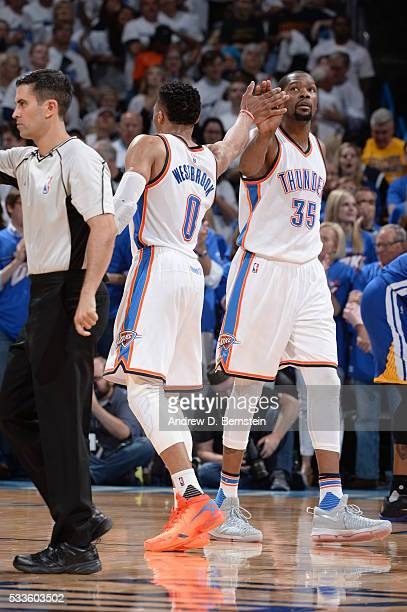 Russell Westbrook of the Oklahoma City Thunder high fives Kevin Durant of the Oklahoma City Thunder during the game against the Golden State Warriors...