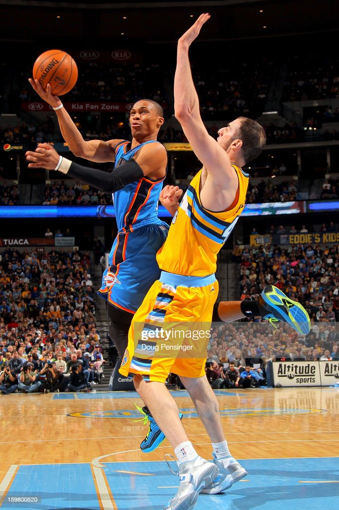 Russell Westbrook #0 of the Oklahoma City Thunder is fouled by Kosta Koufos #41 of the Denver Nuggets as he takes a shot at the Pepsi Center on January 20, 2013 in Denver, Colorado.