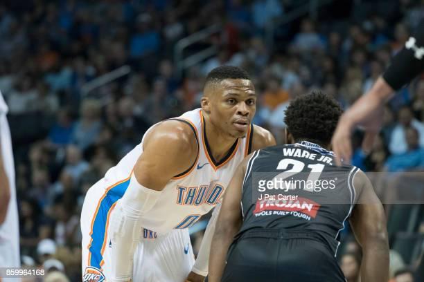 Russell Westbrook of the Oklahoma City Thunder looks at Casper Ware Jr #21 of the Melbourne United during the first half of a NBA preseason game at...