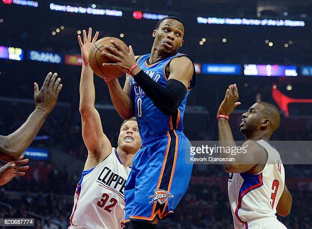 Russell Westbrook of the Oklahoma City Thunder looks to pass the ball under pressure from Chris Paul and Blake Griffin of the Los Angeles Clippers...