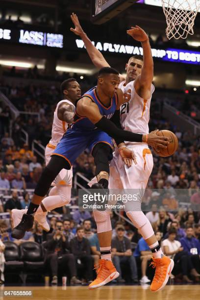 Russell Westbrook of the Oklahoma City Thunder makes a leaping pass around Alex Len of the Phoenix Suns during the first half of the NBA game at...
