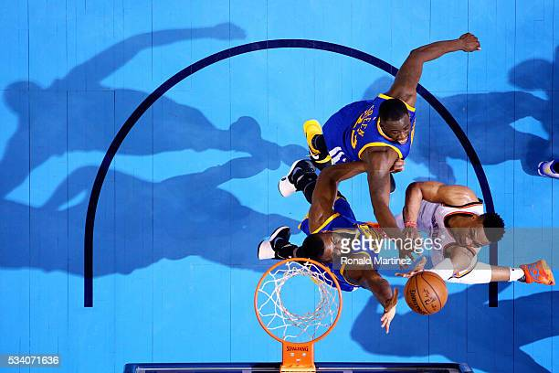 Russell Westbrook of the Oklahoma City Thunder shoots against Draymond Green and Festus Ezeli of the Golden State Warriors in the first half in game...