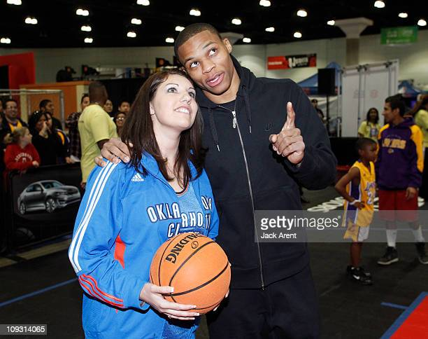 Russell Westbrook of the Oklahoma City Thunder shows a fan where to aim her shot on the Kia court during Jam Session presented by Adidas during All...