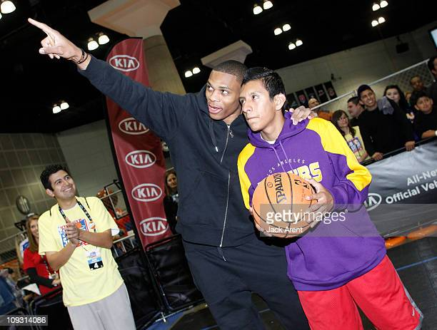 Russell Westbrook of the Oklahoma City Thunder shows a fan where to aim his shot on the Kia court during Jam Session presented by Adidas during All...