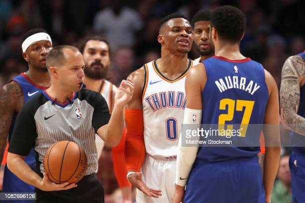 Russell Westbrook of the Oklahoma Thunder is restrained by referee John Goble from Jamal Murray of the Denver Nuggets in the fourth quarter at the...
