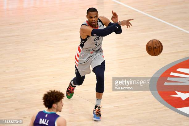 Russell Westbrook of the Washington Wizards passes in front of LaMelo Ball of the Charlotte Hornets during the first half at Capital One Arena on May...