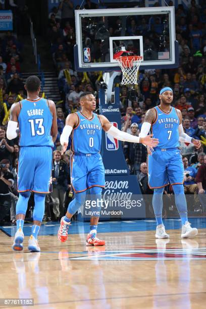 Russell Westbrook Paul George and Carmelo Anthony of the Oklahoma City Thunder looks on during the game against the Golden State Warriors on November...