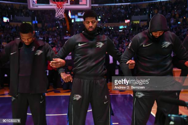 Russell Westbrook Paul George and Carmelo Anthony of the Oklahoma City Thunder honor the National Anthem before the game against the Los Angeles...