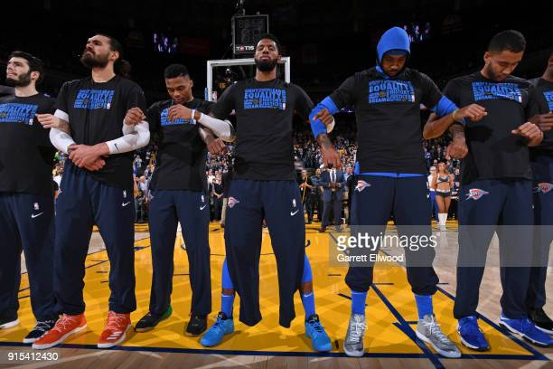 Russell Westbrook Paul George and Carmelo Anthony of the Oklahoma City Thunder stand on the court for the National Anthem before the game against the...