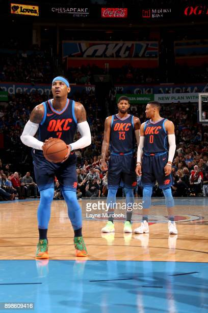 Russell Westbrook Paul George talk while Carmelo Anthony of the Oklahoma City Thunder shoots a free throw against the Houston Rockets on December 25...