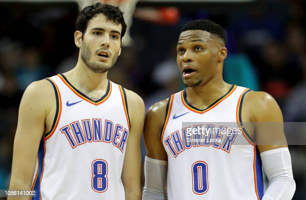 Russell Westbrook talks to teammate Alex Abrines of the Oklahoma City Thunder against the Charlotte Hornets during their game at Spectrum Center on...