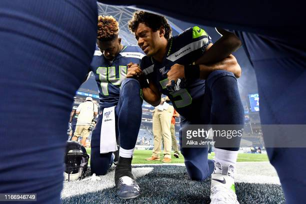 Russell Wilson and DK Metcalf of the Seattle Seahawks have a prayer after the preseason game victory over the Denver Broncos at CenturyLink Field on...